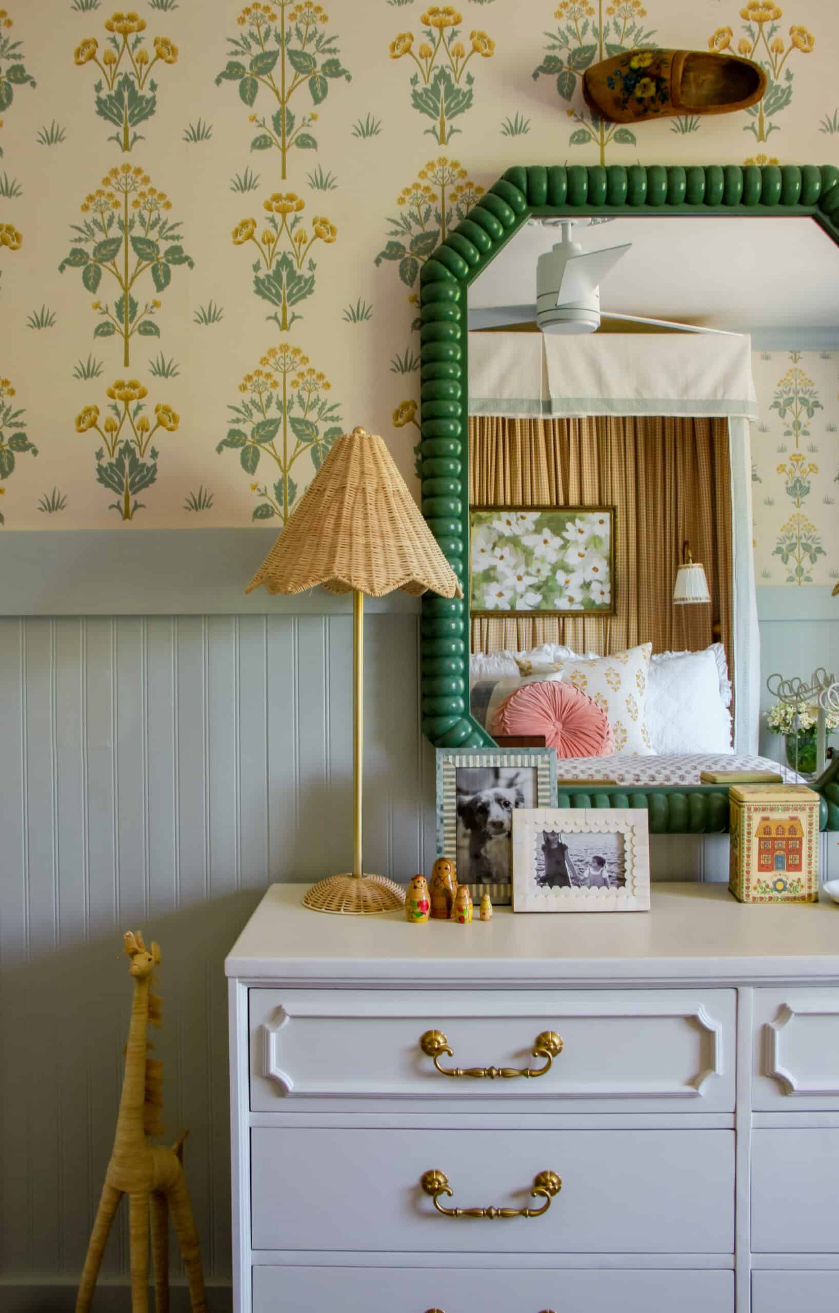 white dresser with green mirror and rattan lamp