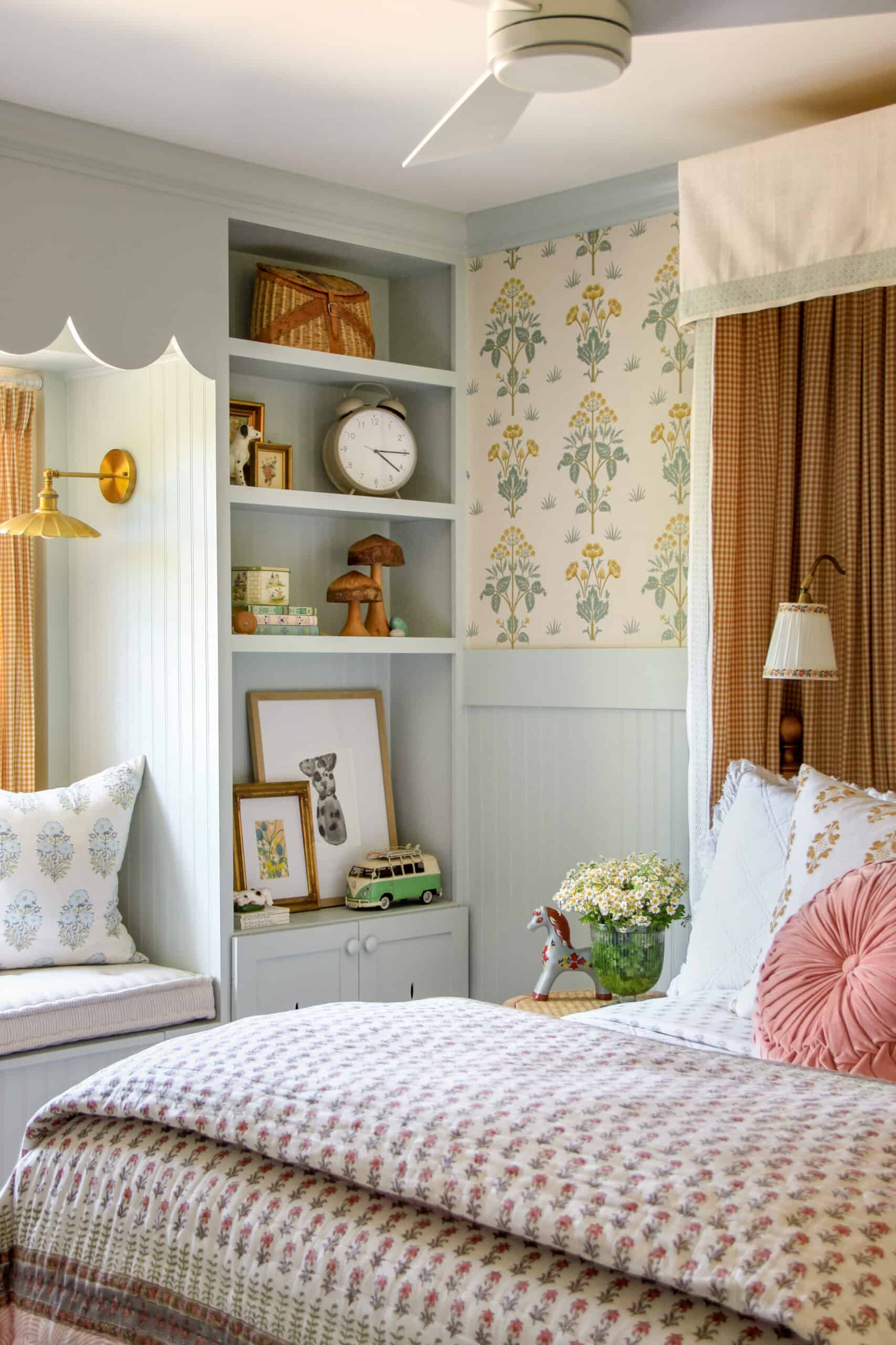 corner of collected cottage-inspired bedroom with blue paint and wallpaper
