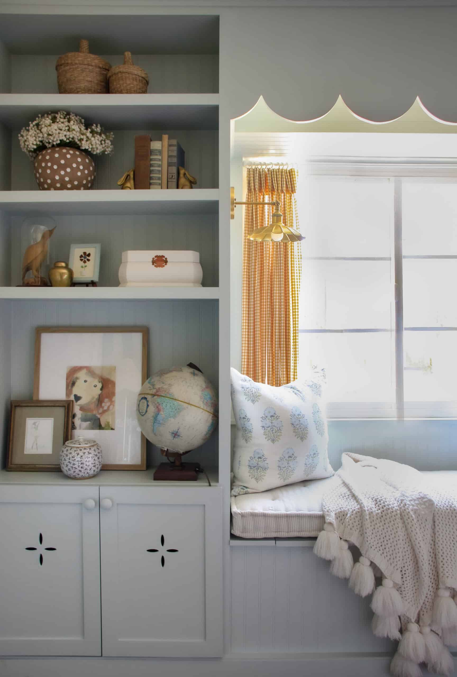 light blue built in shelving with window seat