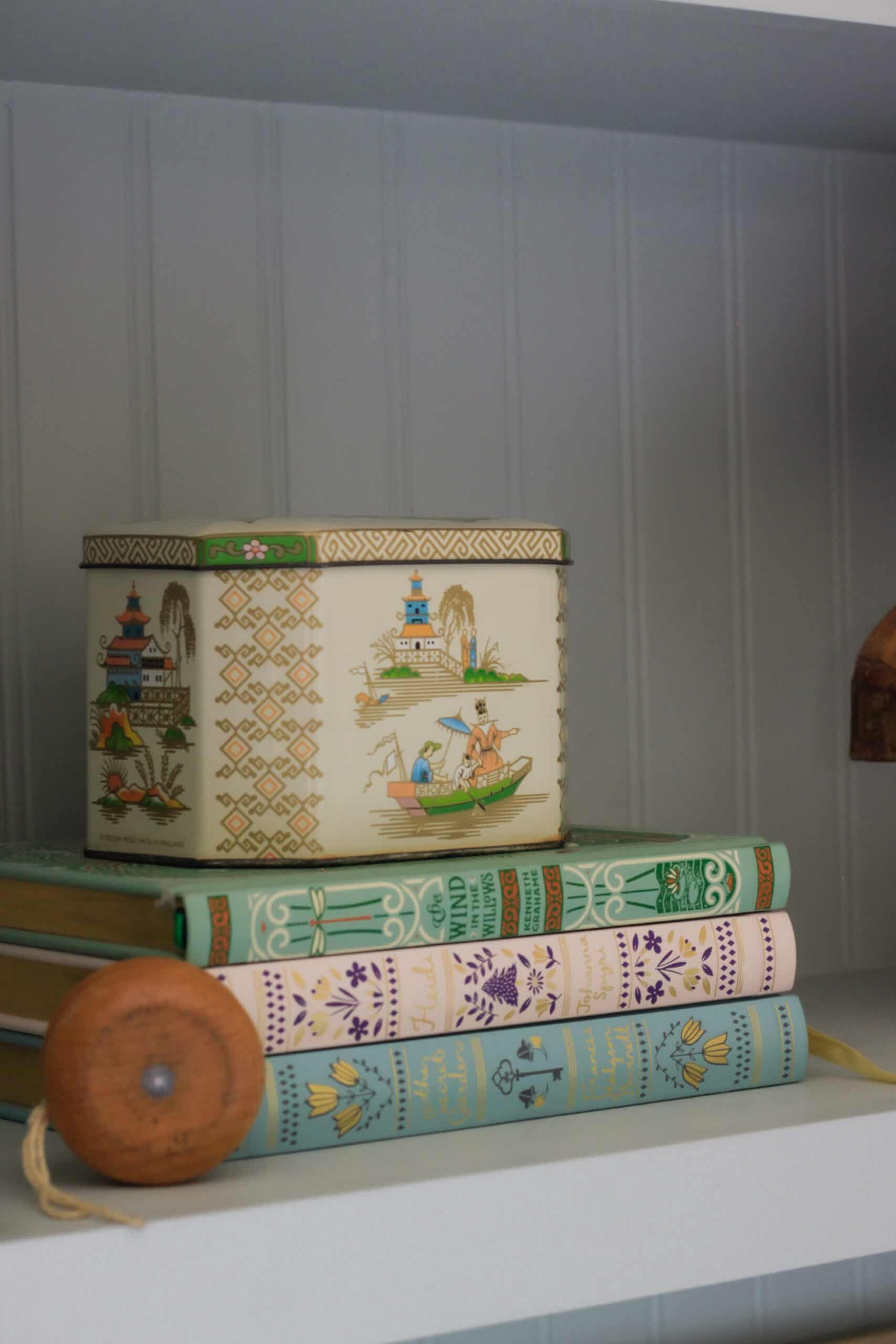 vintage Chinese tin sitting on a stack of colorful books