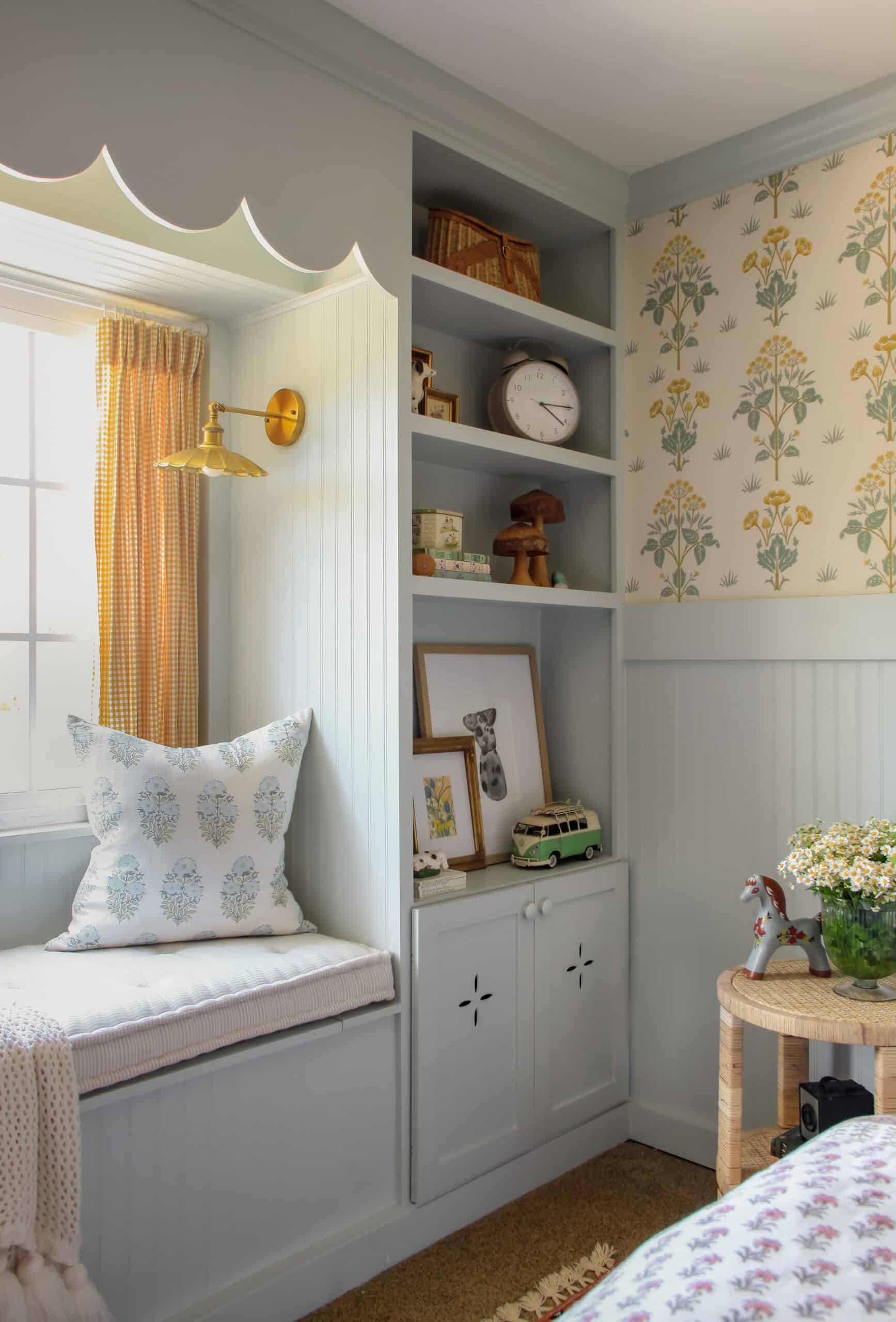 corner of girl's cottage-inspired bedroom with blue built ins and wallpaper