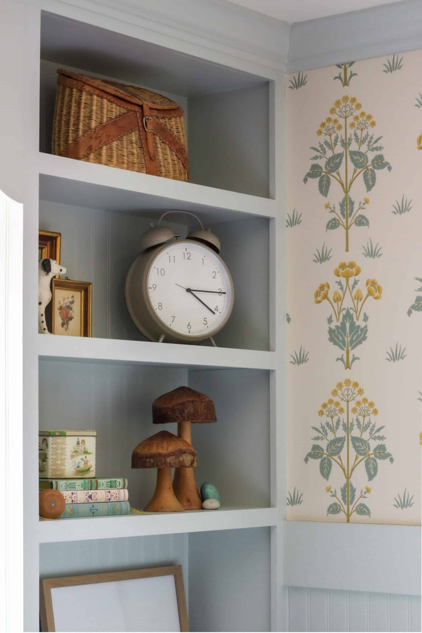 blue corner shelf with decor next to wallpapered wall