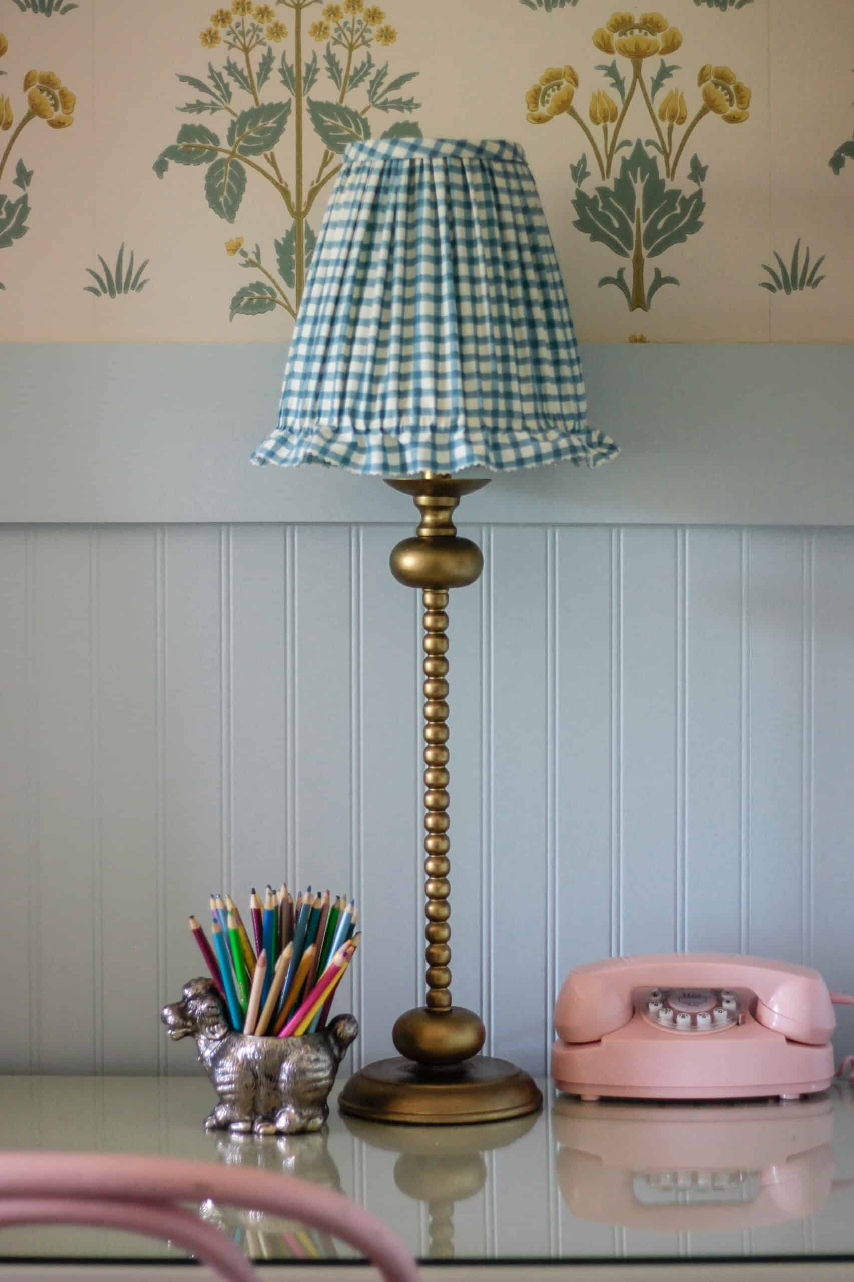 brass desk lamp with blue gingham shade on desk with pink phone