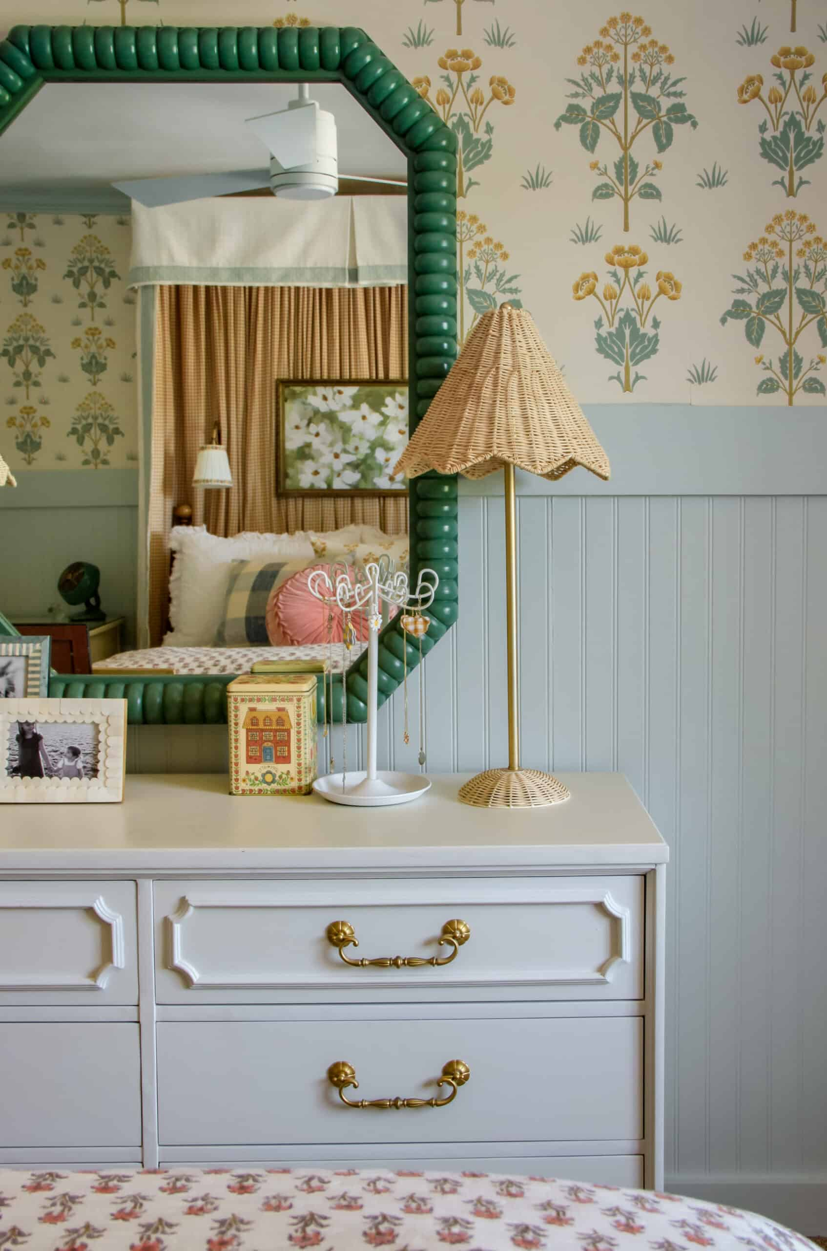 white dresser with rattan lamp and green mirror over it