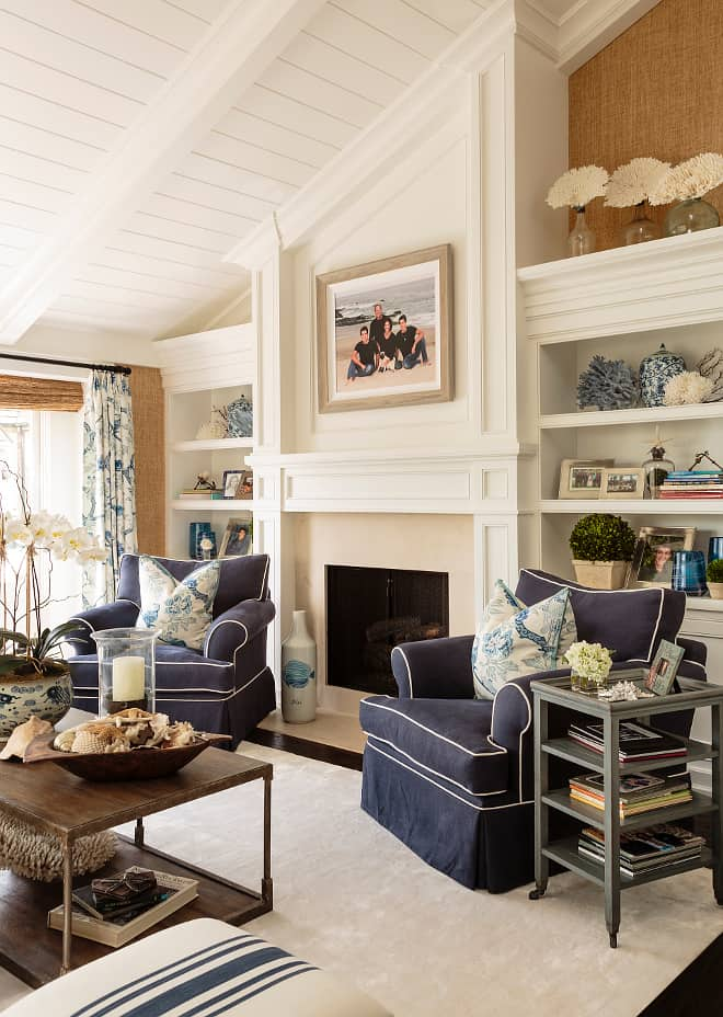 living room with slanted fireplace, bookcases, and two chairs