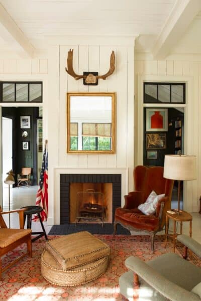 living room with vertical shiplap fireplace and antlers above
