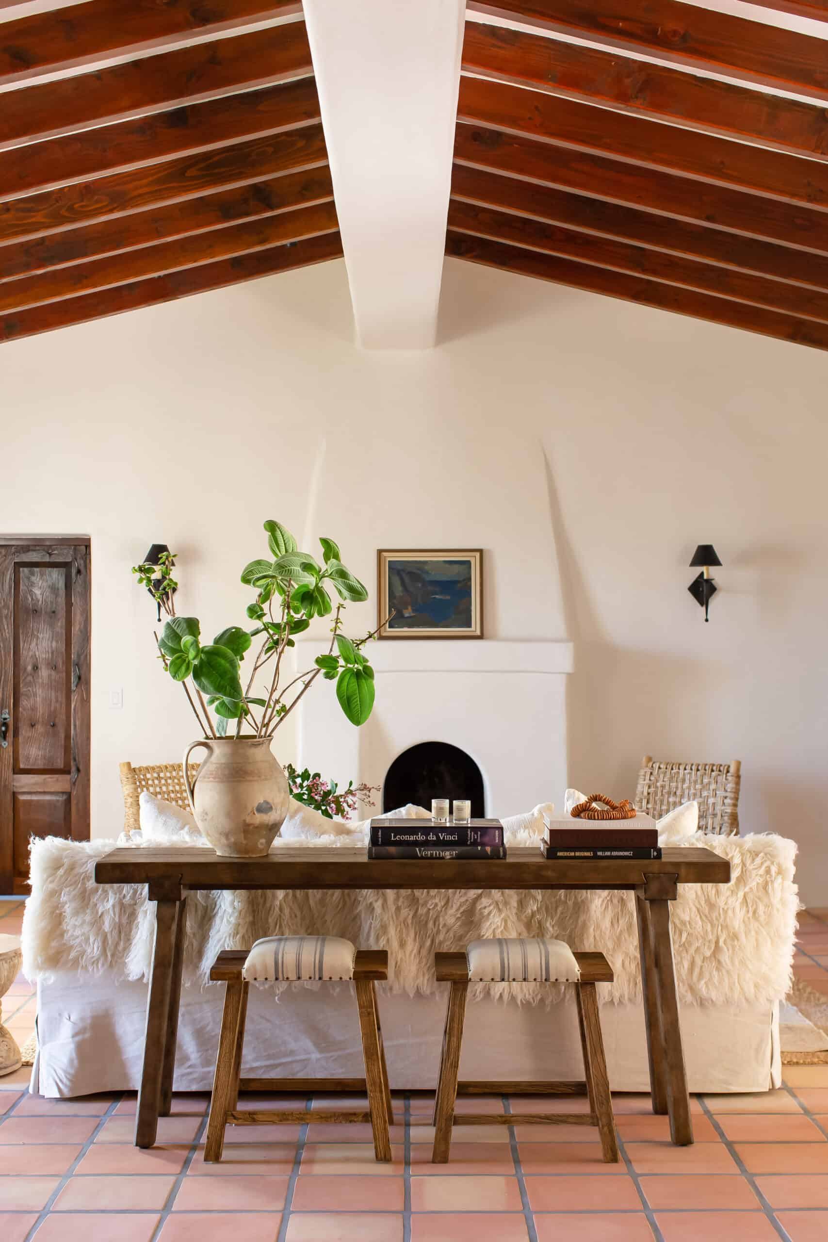 spanish style living room with plaster fireplace and beams on ceiling