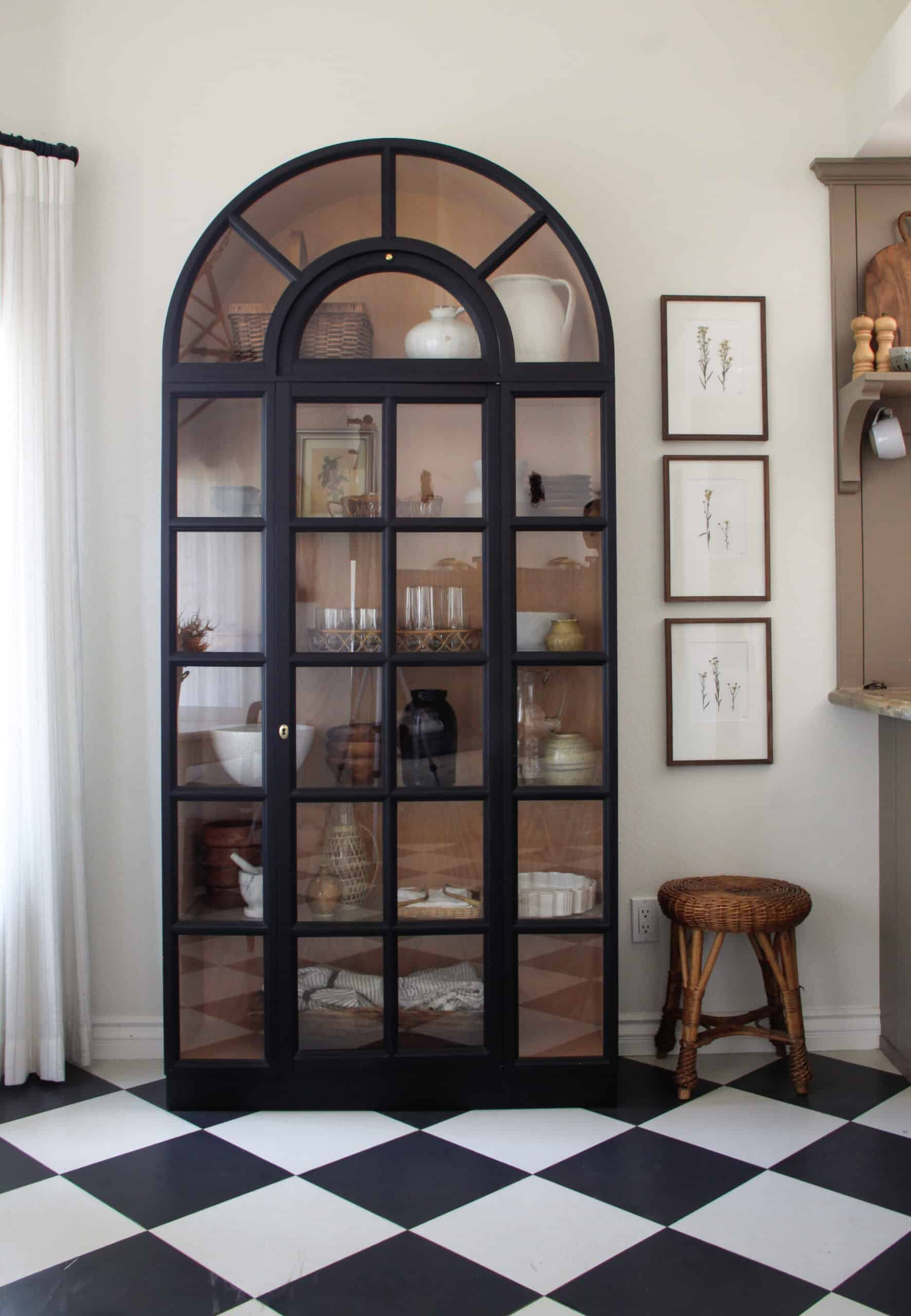 black arched cabinet on black and white harlequin floors