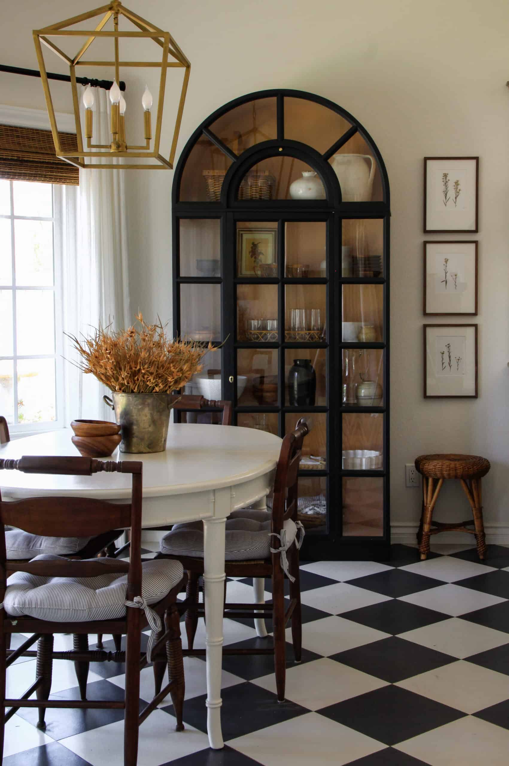 breakfast nook with checkered floors and wheat on the table in front of cabinet