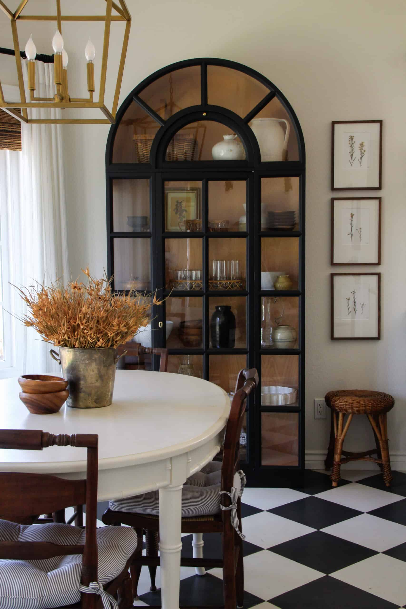 black arched display cabinet in breakfast nook with white table and checkered floors