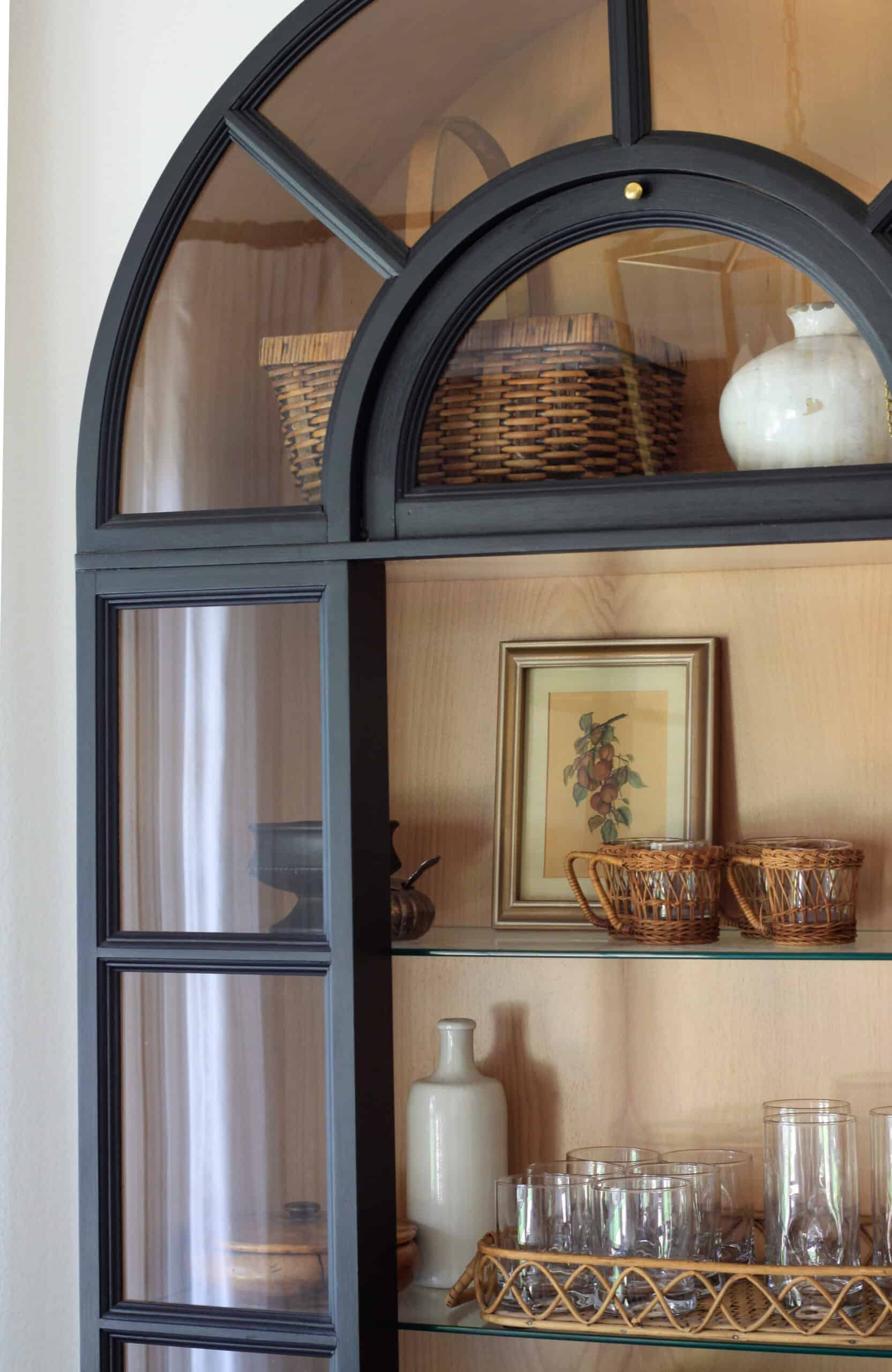 black arched cabinet with door open and styling pieces inside