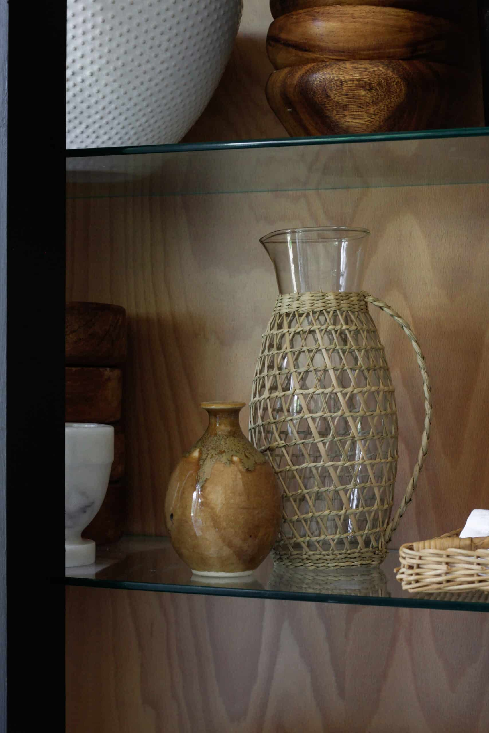 glass pitcher with rattan outside and little ceramic piece sitting on shelf