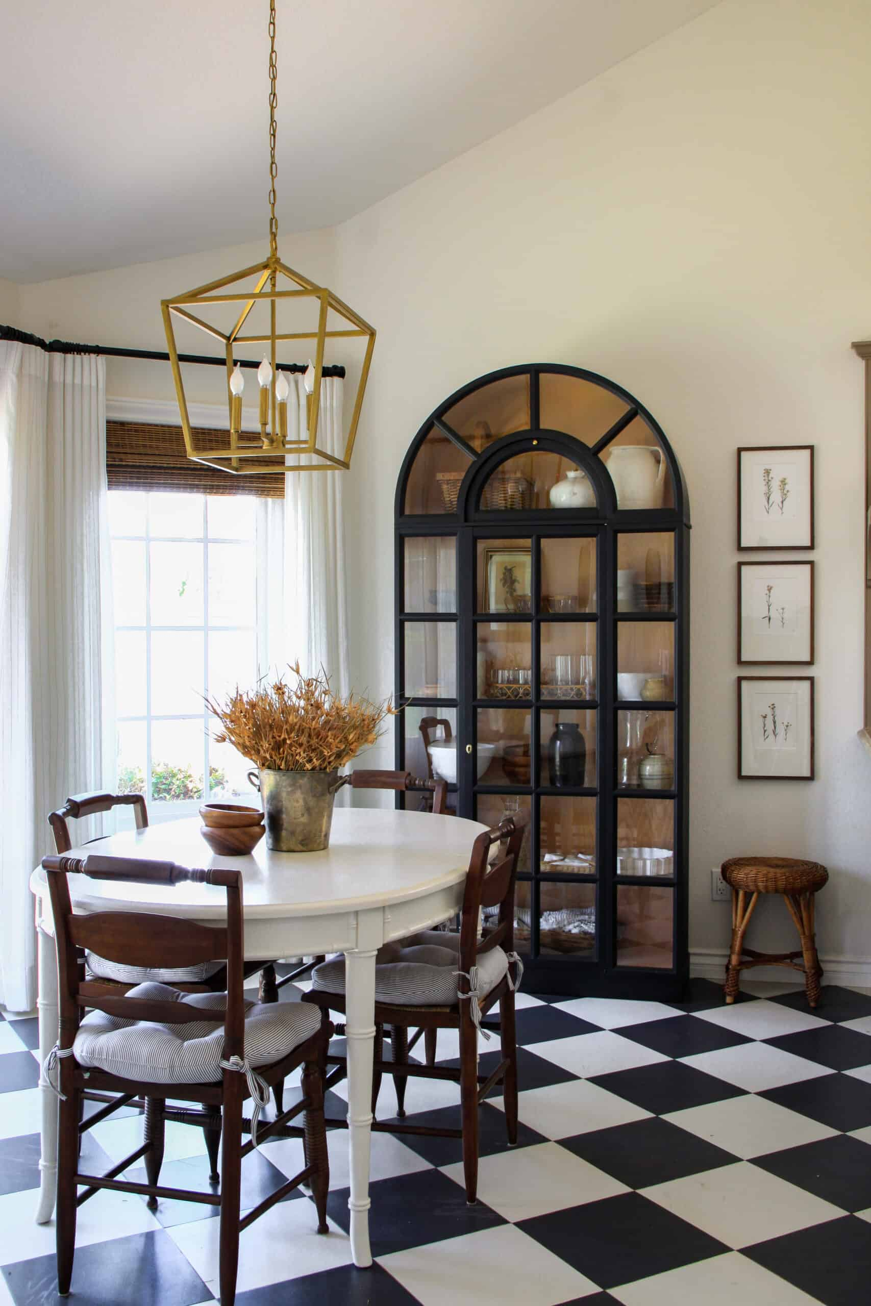 breakfast nook with checkered floors, white table, black cabinet and gold light fixture
