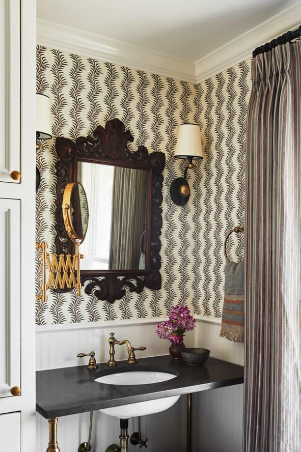 powder room with walnut mirror, sconces and wallpaper