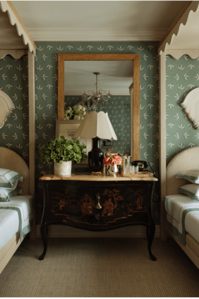 bedroom with twin beds, wallpaper and chest and mirror between