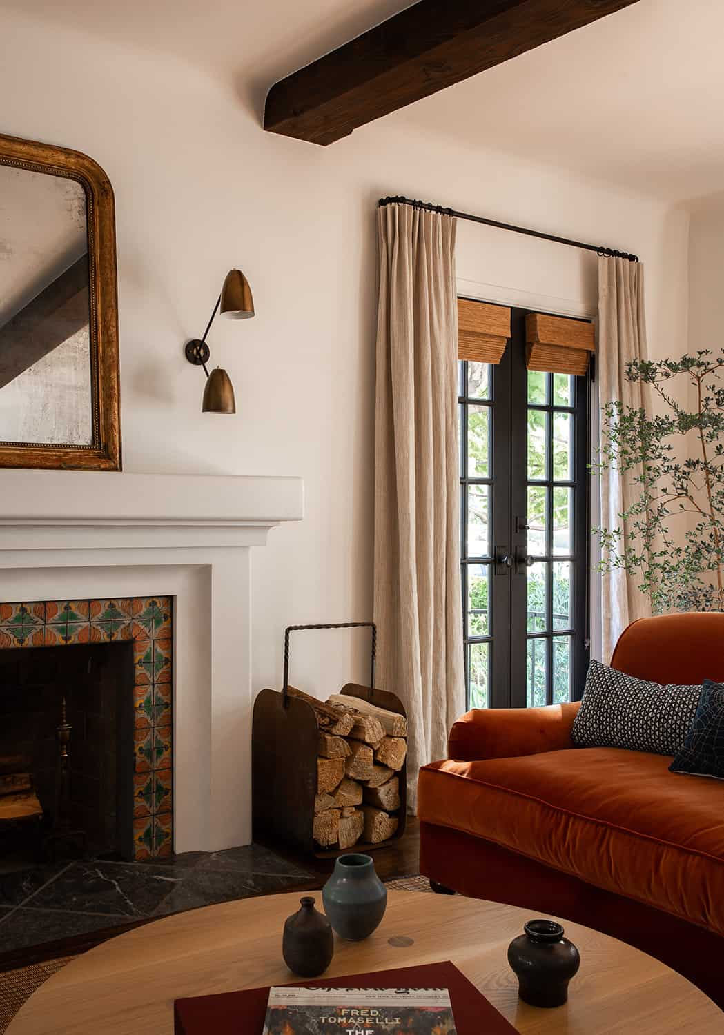 living room with orange velvet sofa and logs by fireplace