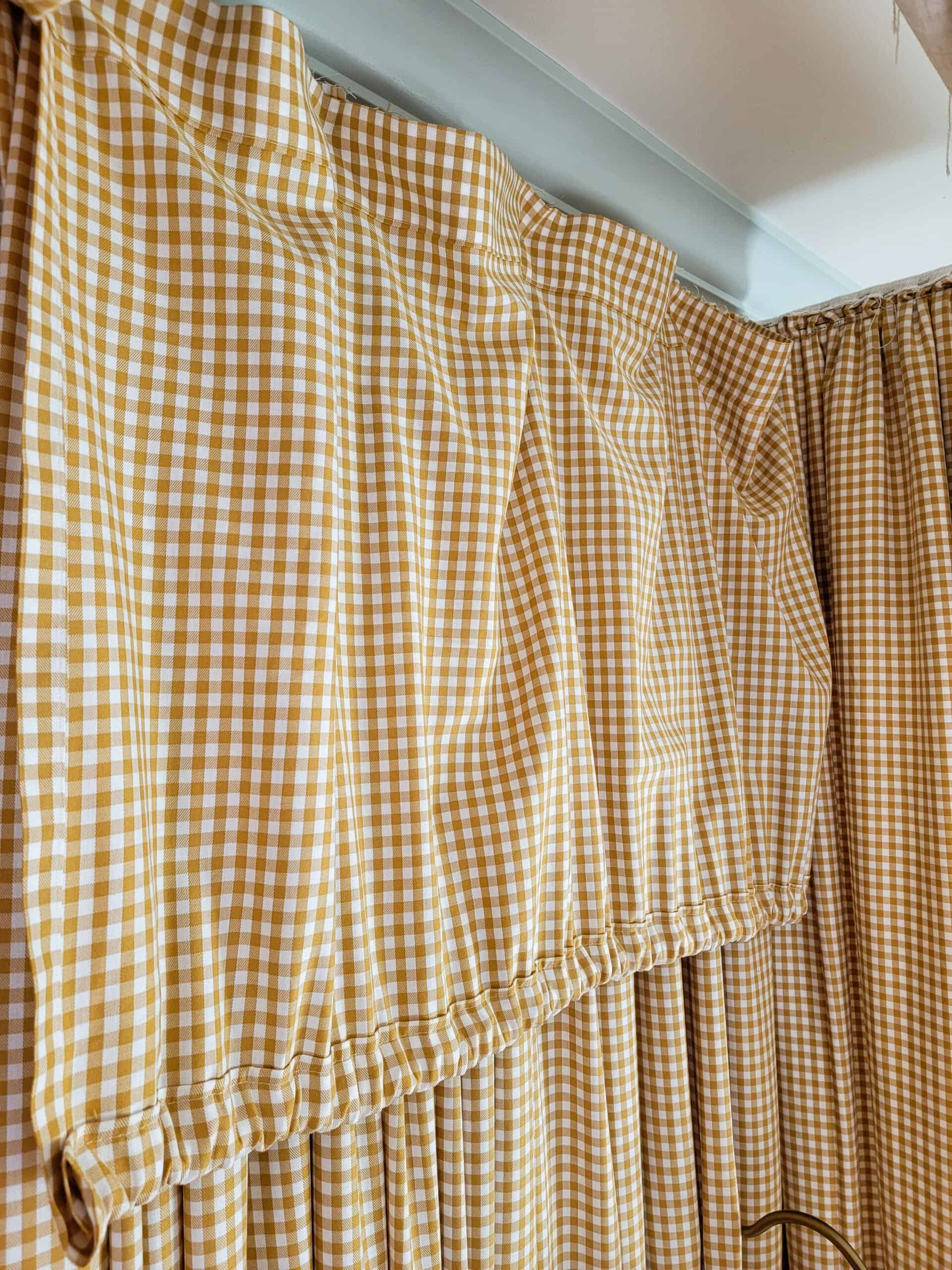 yellow gingham fabric hanging from canopy frame