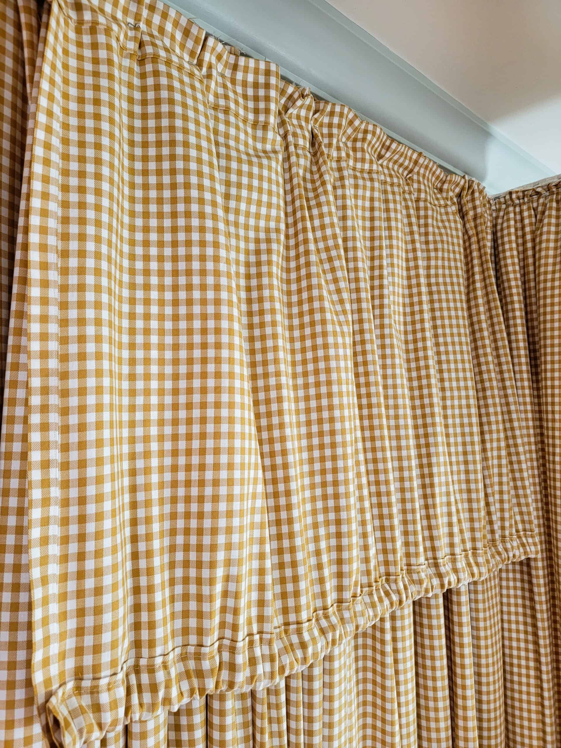 yellow gingham fabric gathered onto a wooden canopy frame
