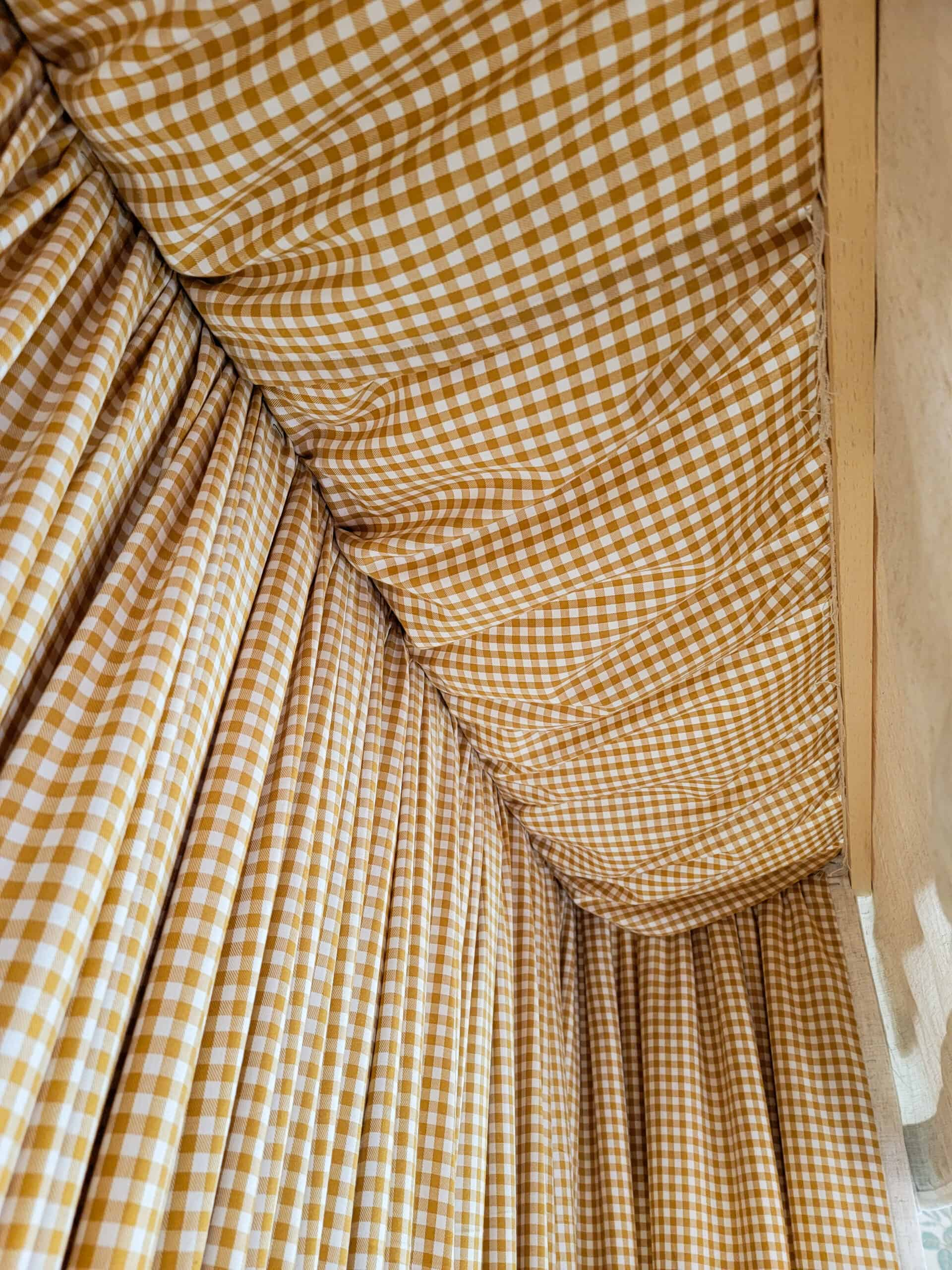 yellow gingham fabric on top of a fabric headboard canopy