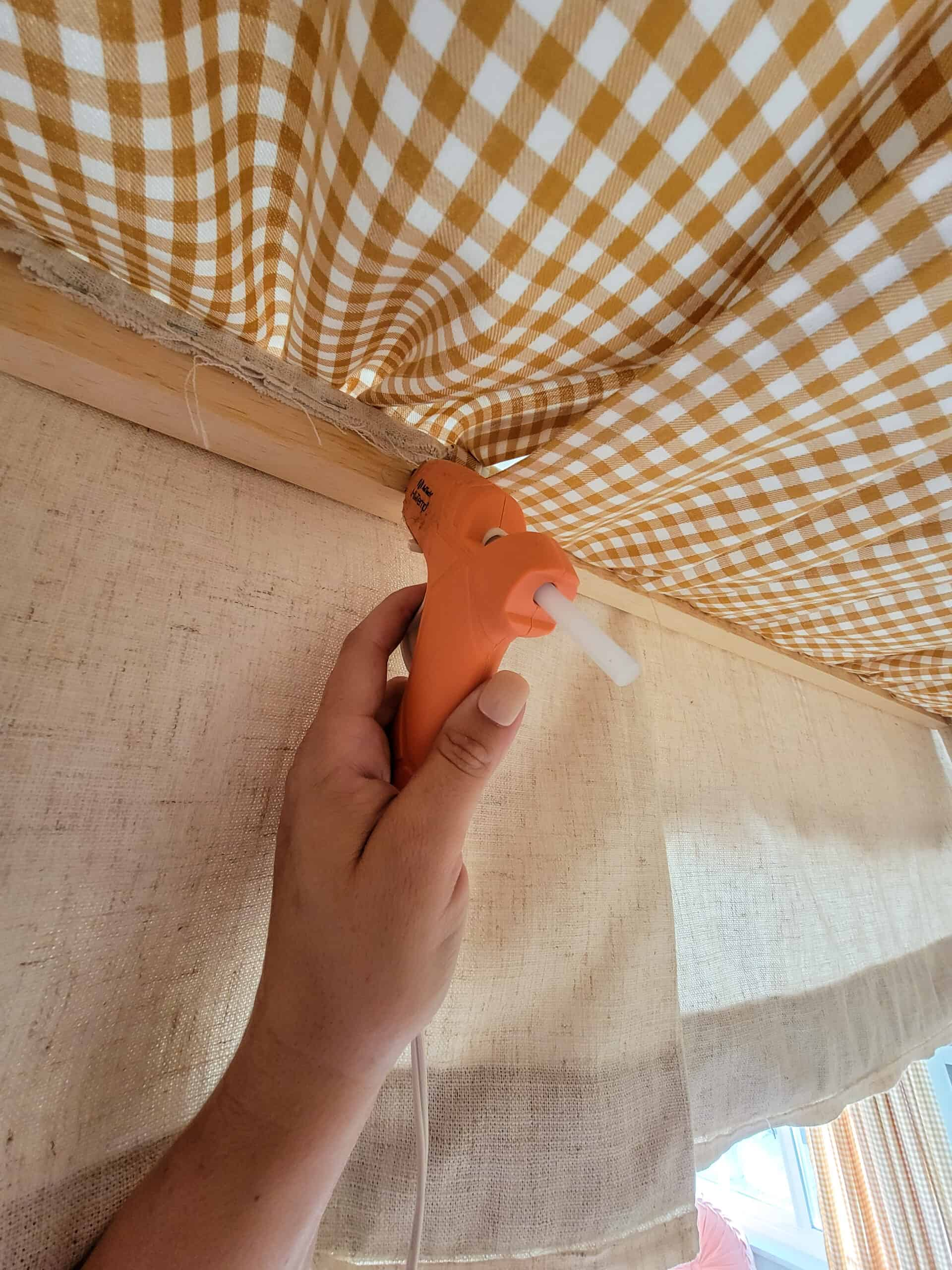hand with hot glue gun attaching yellow gingham fabric to canopy frame