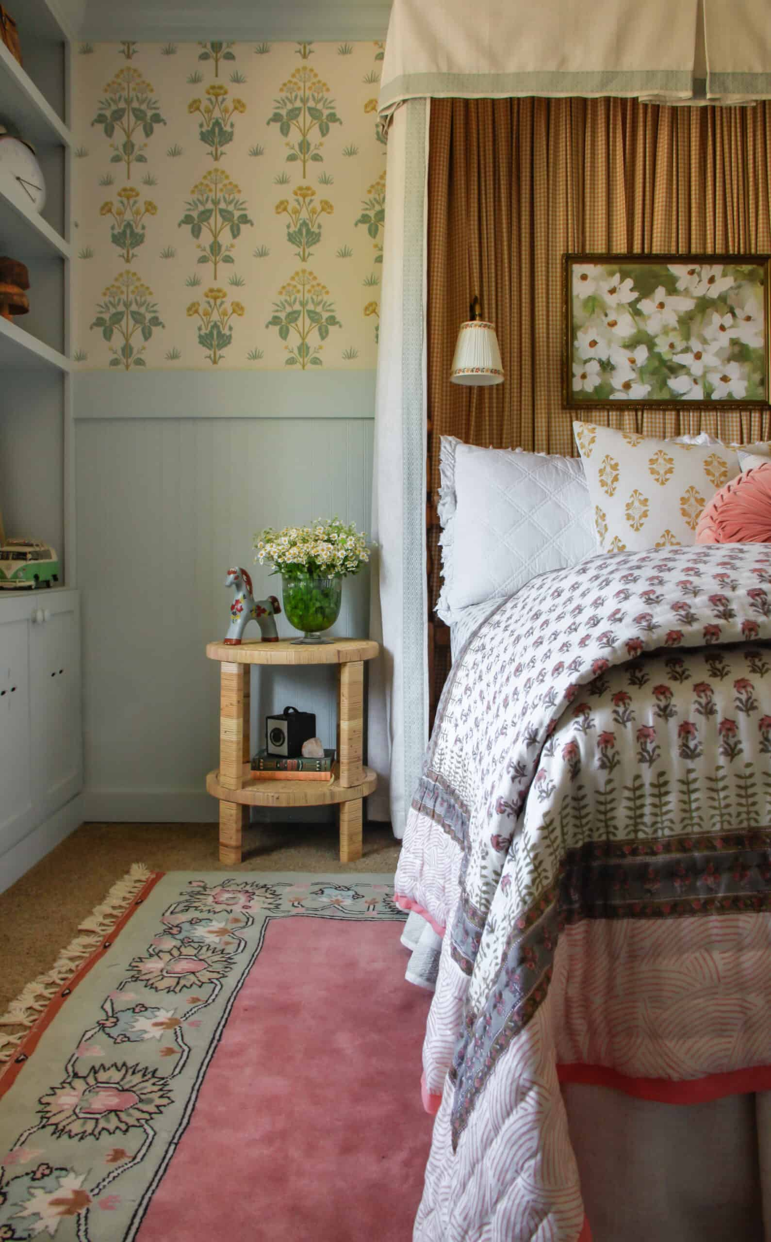 girl's bedroom with pink rug, wallpaper and headboard canopy