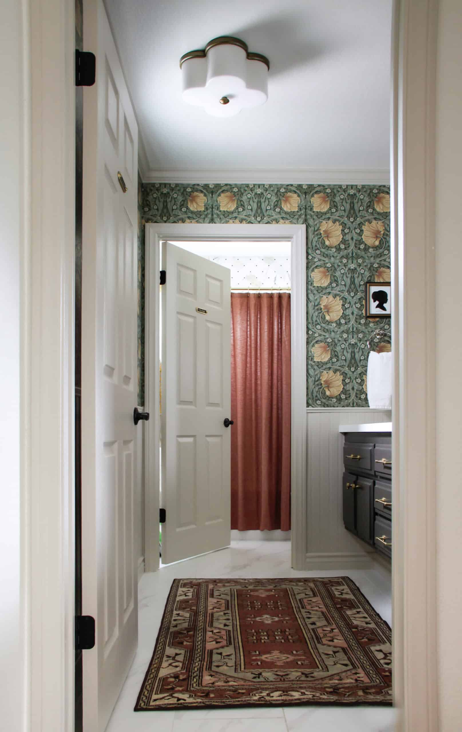 bathroom with green floral wallpaper and vintage rug
