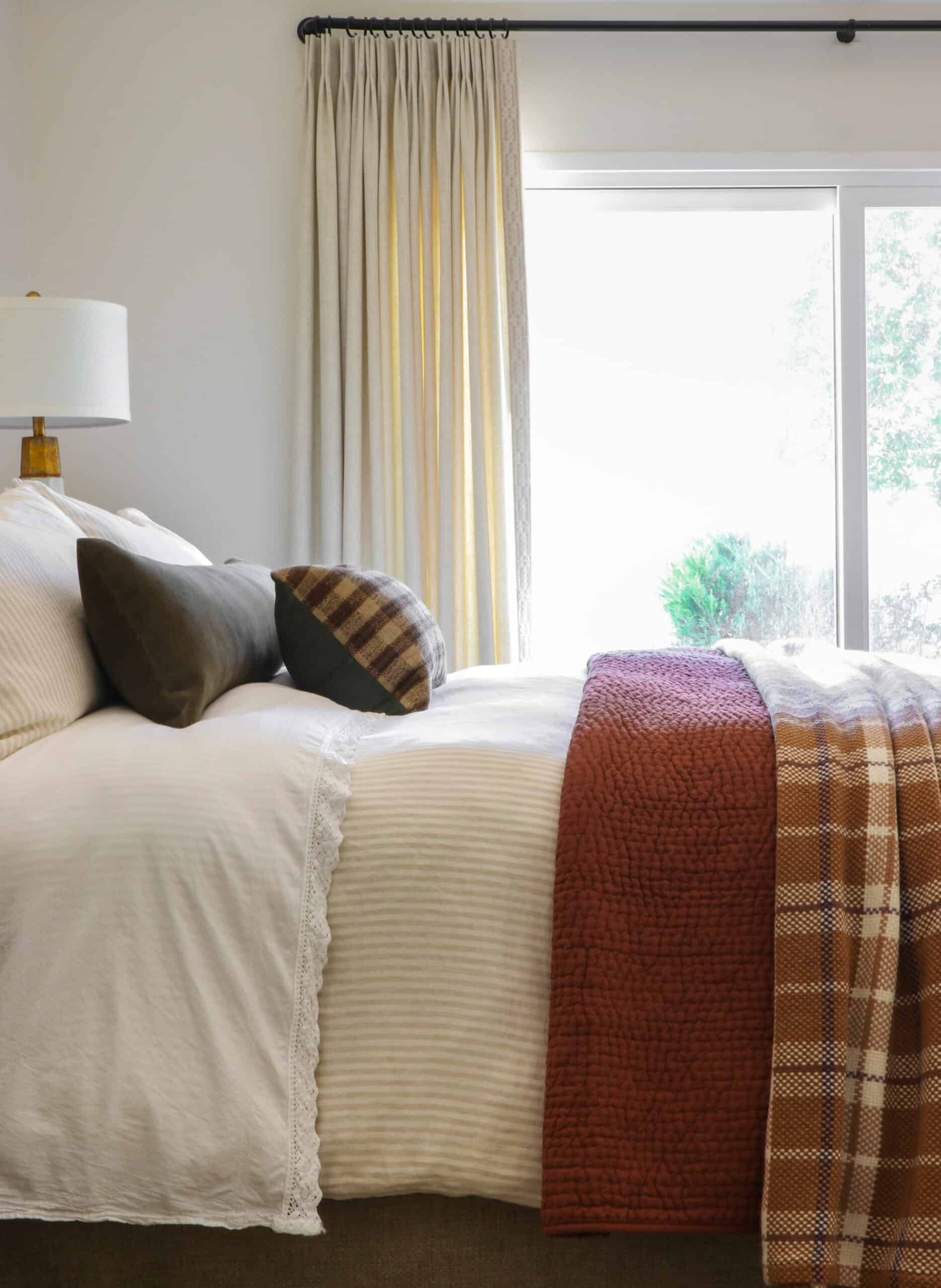 side view of bed with rust and plaid bedding
