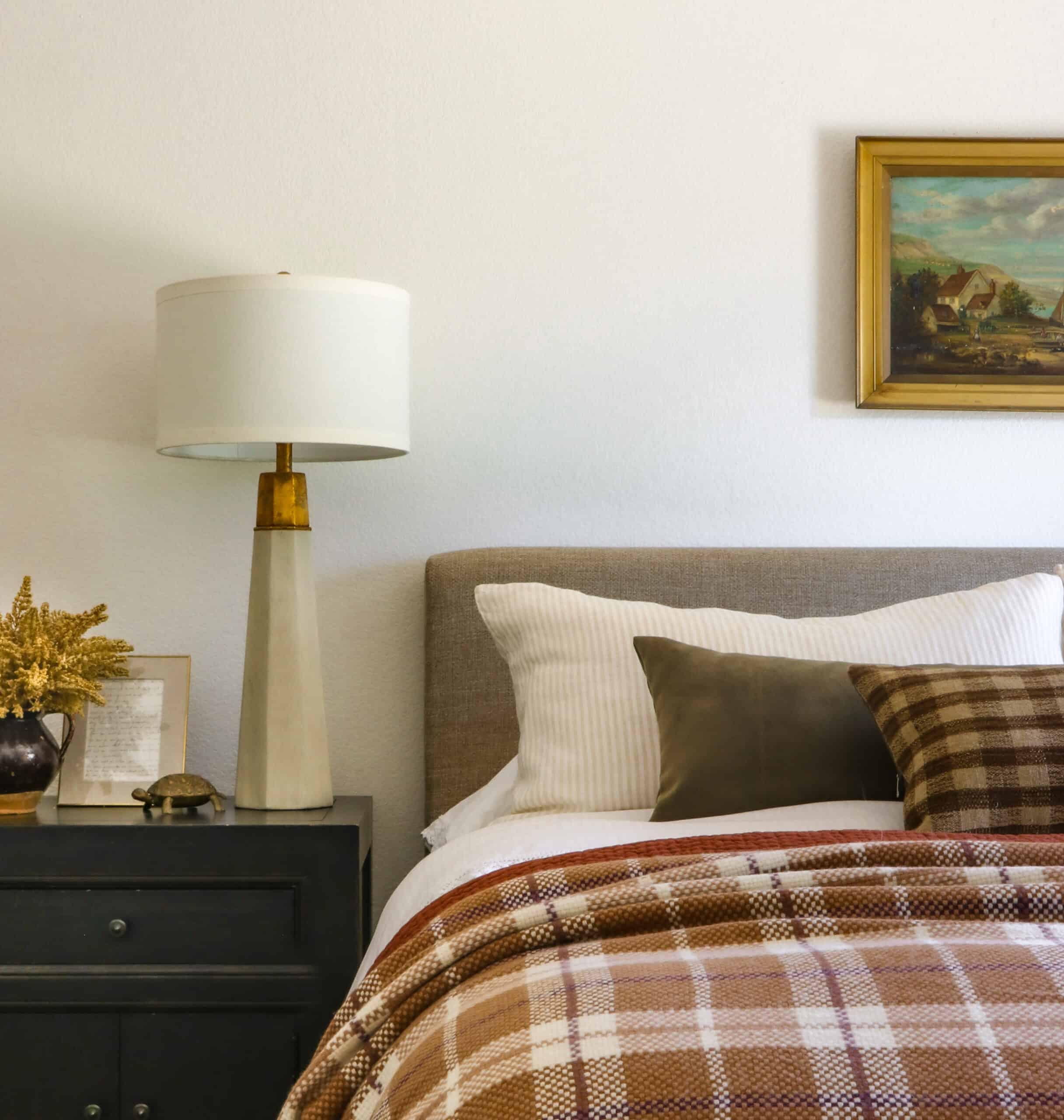 closeup of bed with plaid bedding and velvet pillow