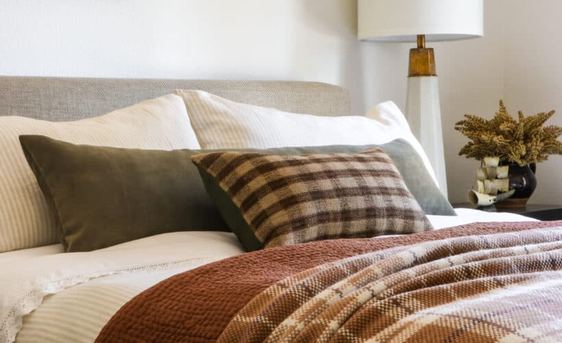 plaid and rust bedding on bed with oil painting above