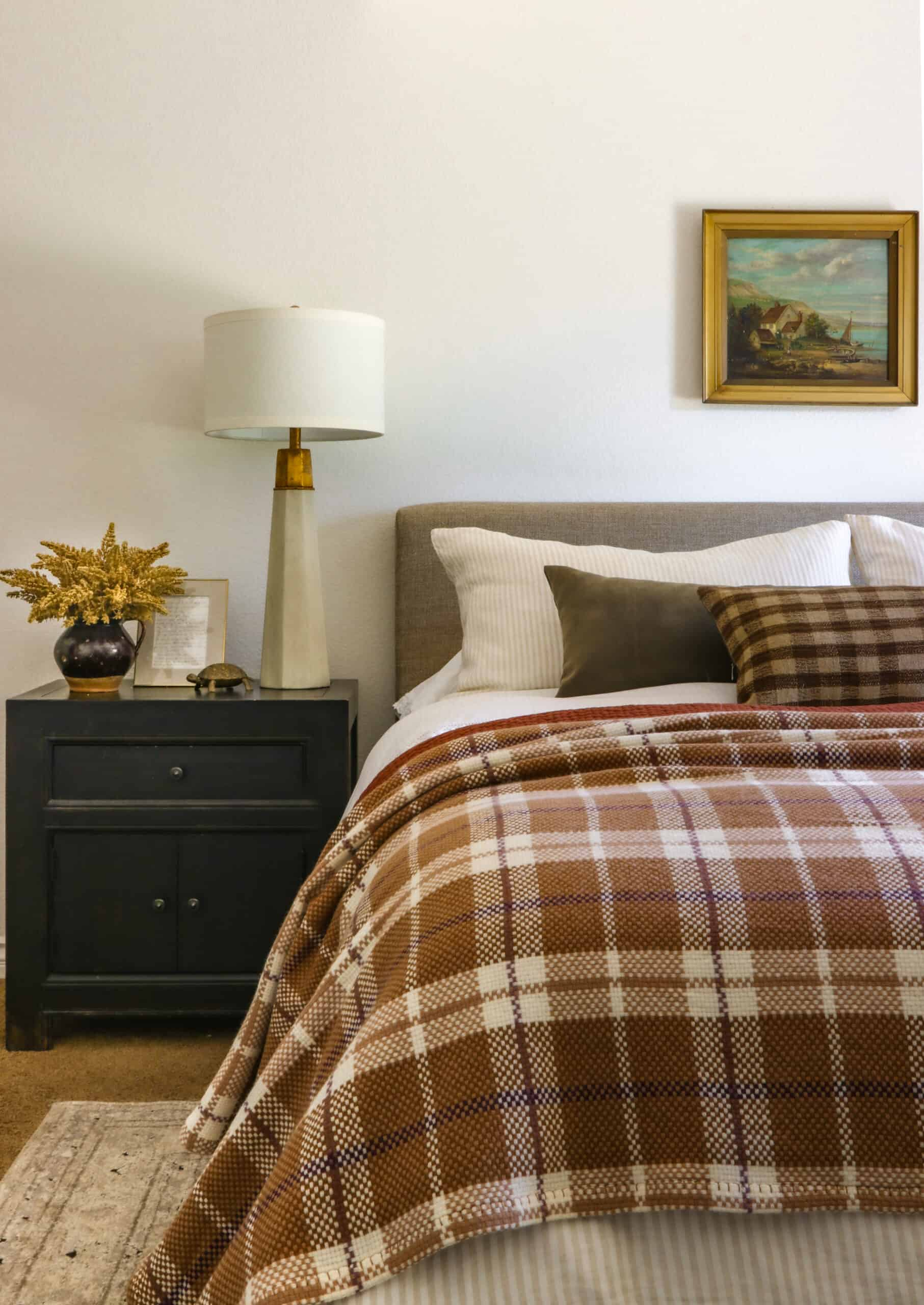 plaid and rust bedding on bed with oil painting above and nightstand beside