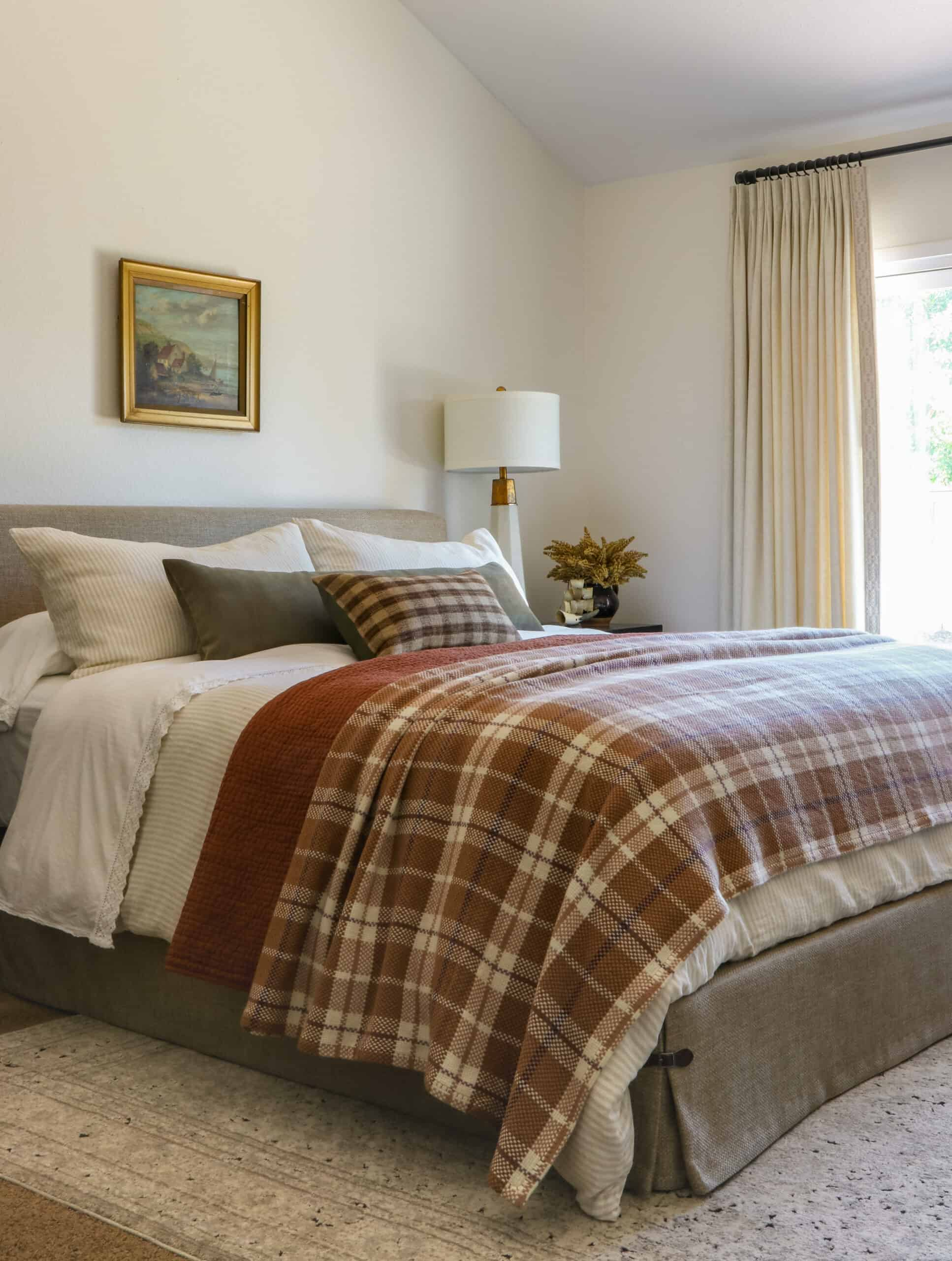 master bedroom with rust and plaid bedding and cream curtains