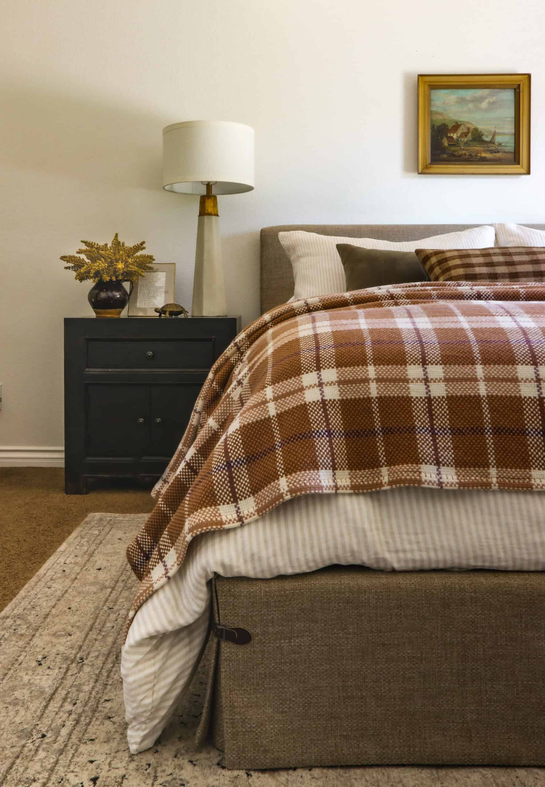 side view of bedroom with plaid bedding and black nightstand