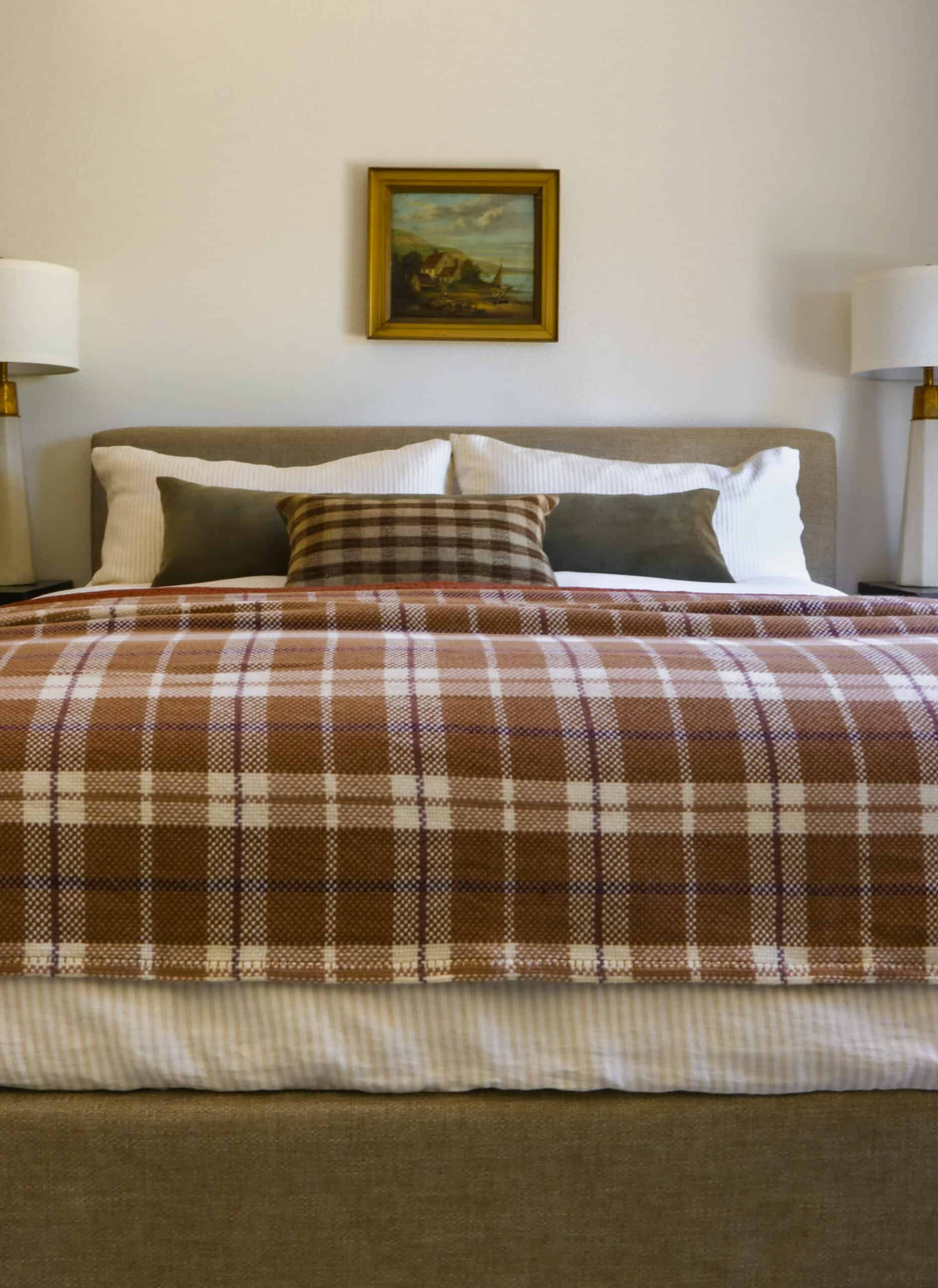 straight on shot of master bed with plaid bedding and oil painting above
