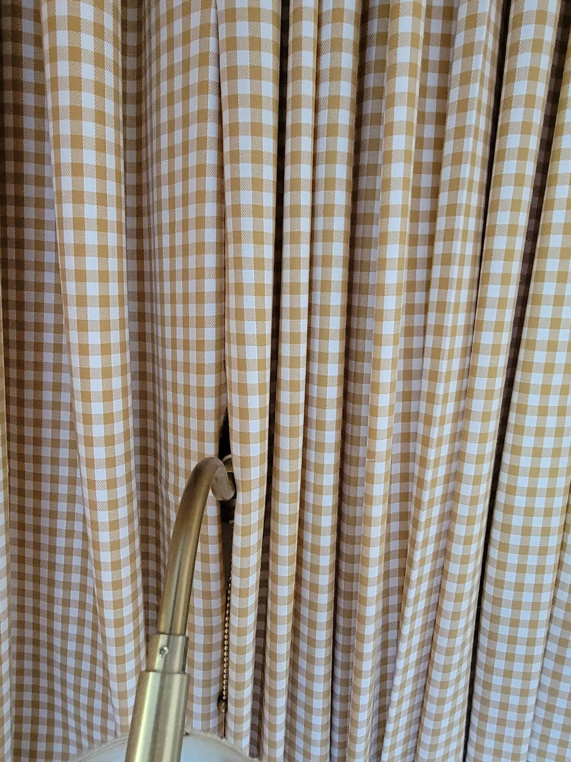 gingham fabric surrounding a brass sconce