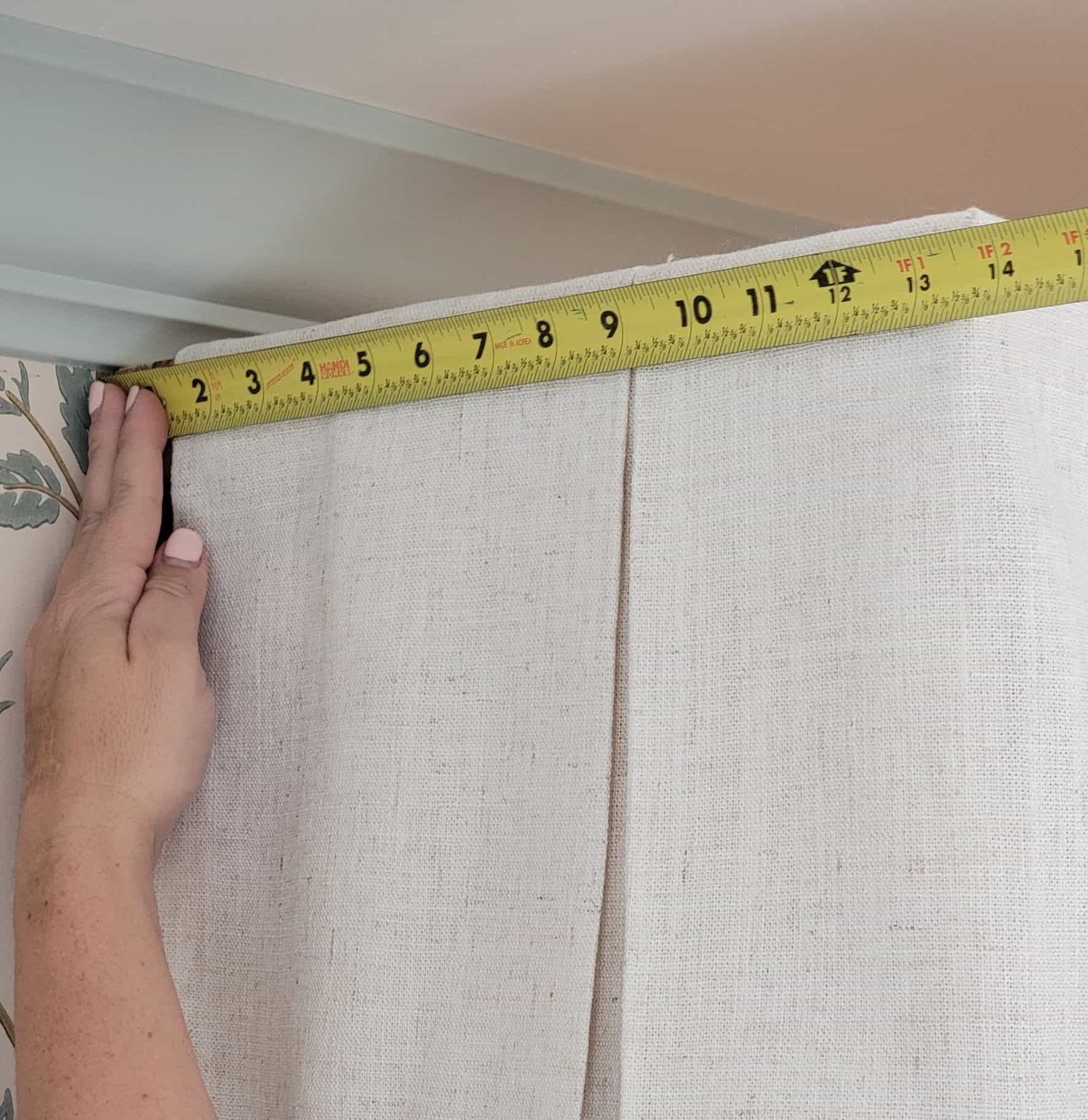hand holding a yellow tape measure on headboard canopy